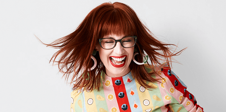 A colourful woman laughing and shaking her hair