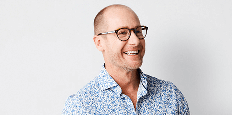 A happy looking man in a floral shirt wearing glasses